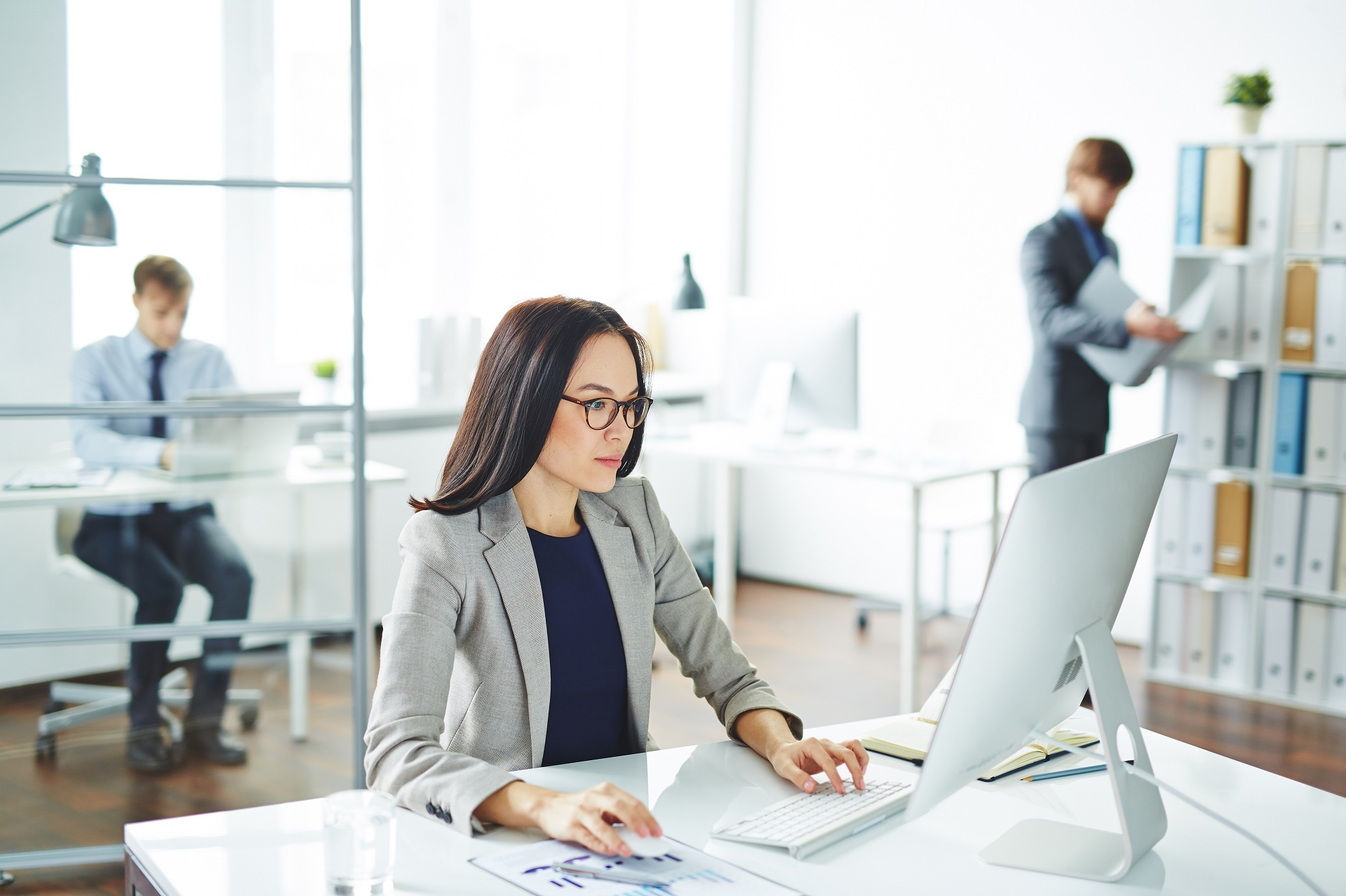 Pretty office worker typing in working environment